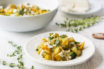 Feta & zucchini low carb side dish on white plate with sprigs of thyme