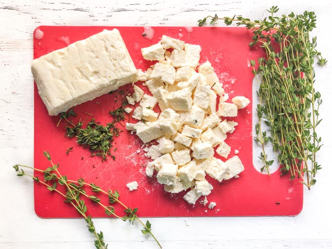 red cutting board with sprigs of thyme and feta cheese
