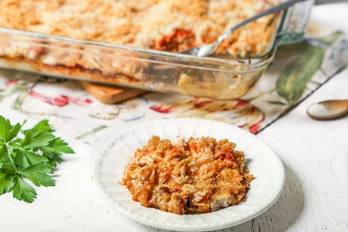 baking dish of chicken parmesan casserole and white plate with a serving and parsley