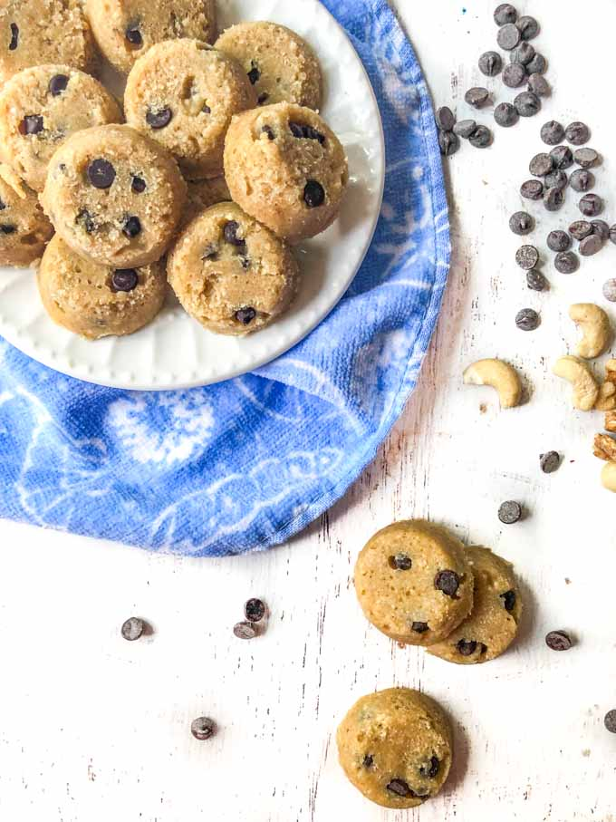 white plate of keto cookie dough fat bombs with scattered chocolate chips and blue towel