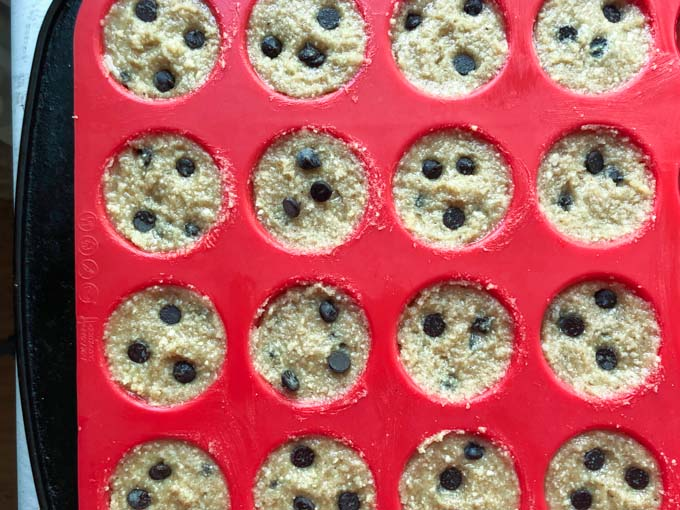 red silicone mini muffin pan with raw keto cookie dough