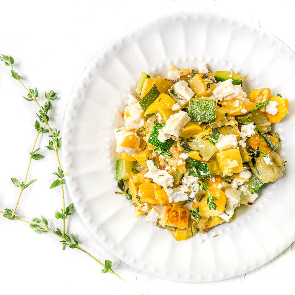 white plate with feta and zucchini side dish and sprigs of thyme