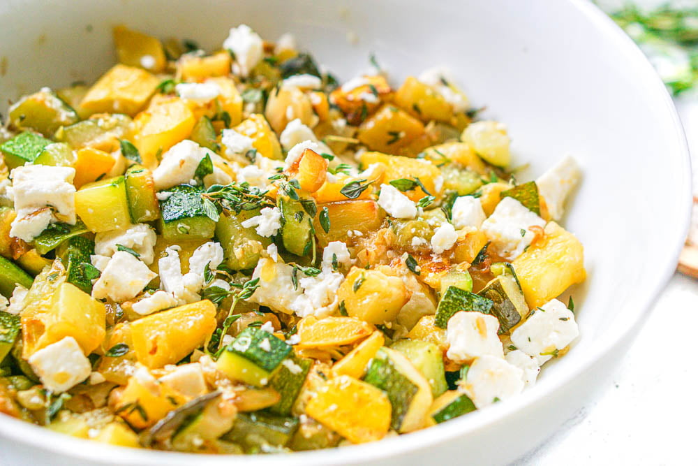 closeup of a white bowl filled with yellow zucchini and chunks of feta and fresh thyme leaves