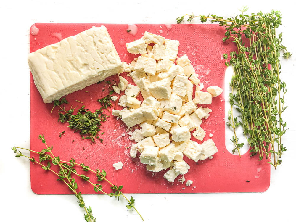 red cutting board with a chunks and a block of feta cheese and fresh thyme sprigs