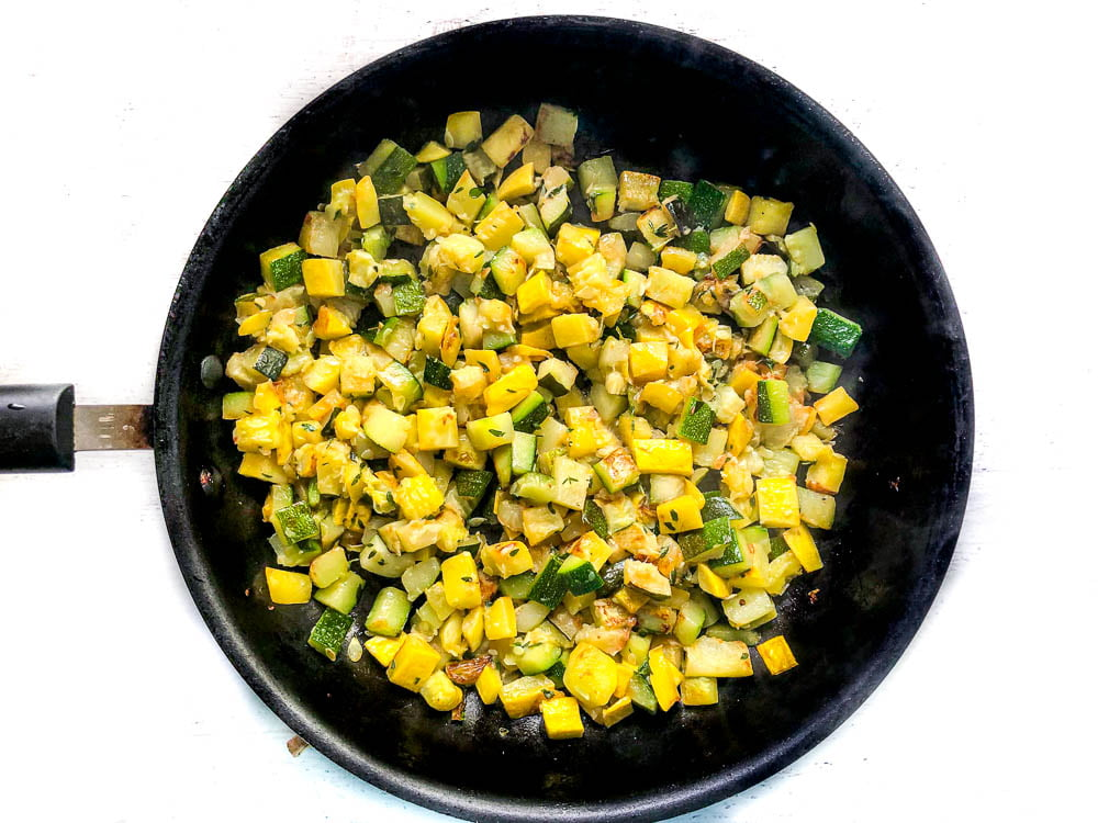 black skillet with sauted yellow and green zucchini