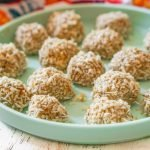 blue plate with keto pumpkin seed balls covered in toasted coconut