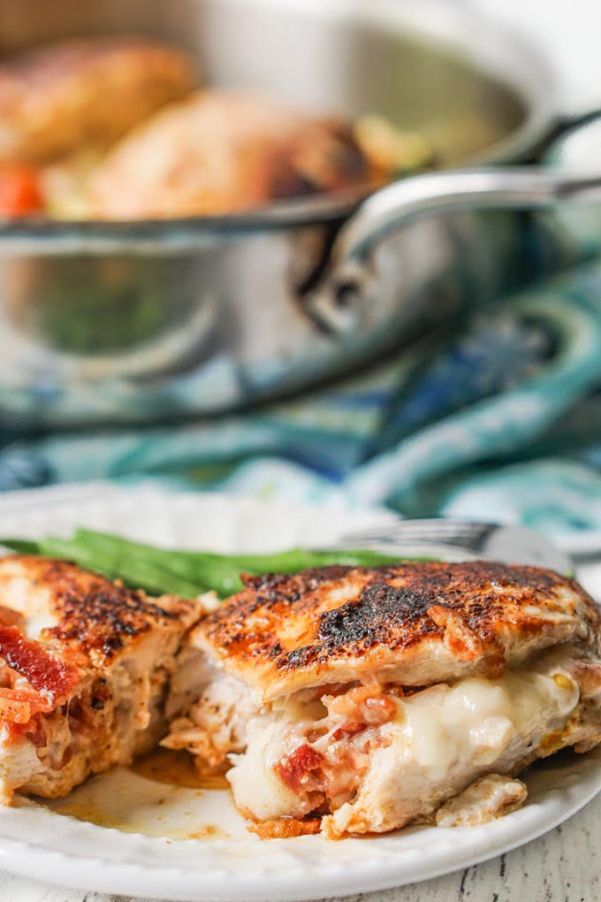 closeup of cut stuffed chicken breast with pan in background