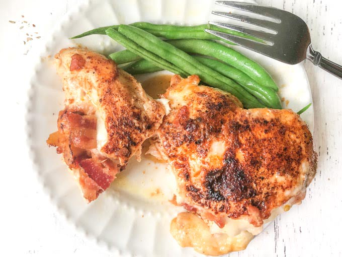 white plate with cheese and bacon stuffed chicken breast and green beans