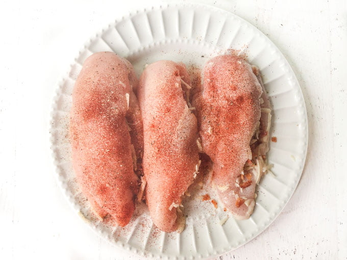 raw stuffed chicken breasts with spices on white plate