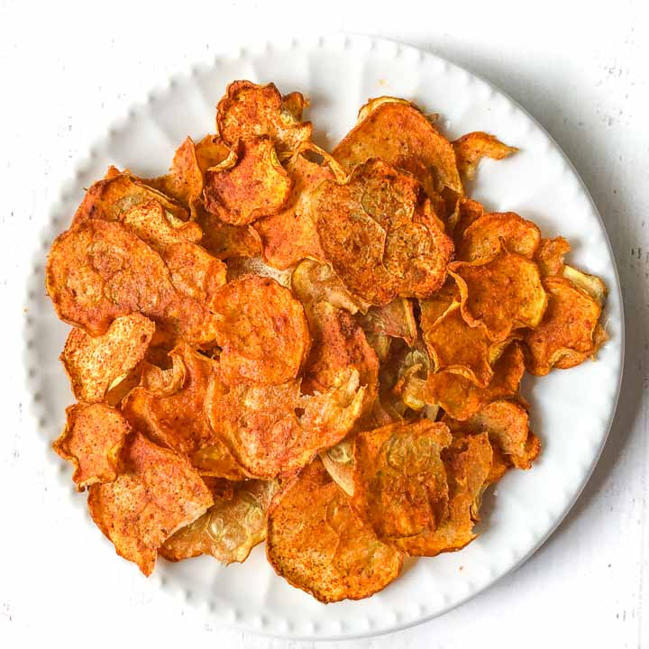 white plate with nacho flavored zucchini chips