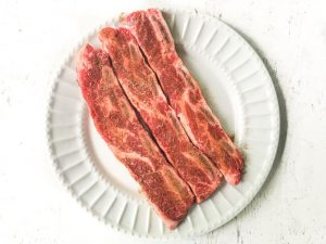 white plate with raw ribs with rub