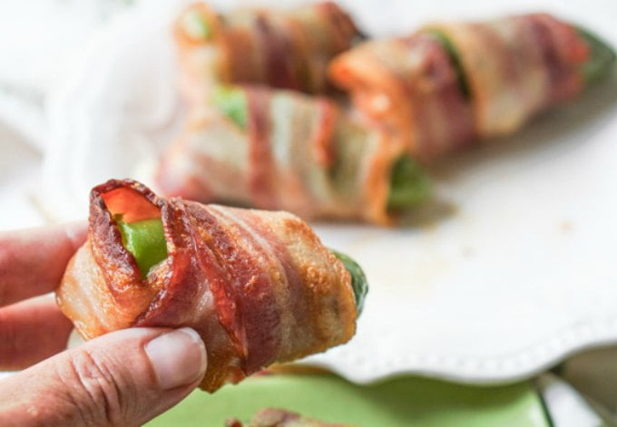 fingers holding bacon wrapped jalapeno