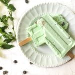 white plate with two mint chocolate chip keto ice pops with fresh mint and chips