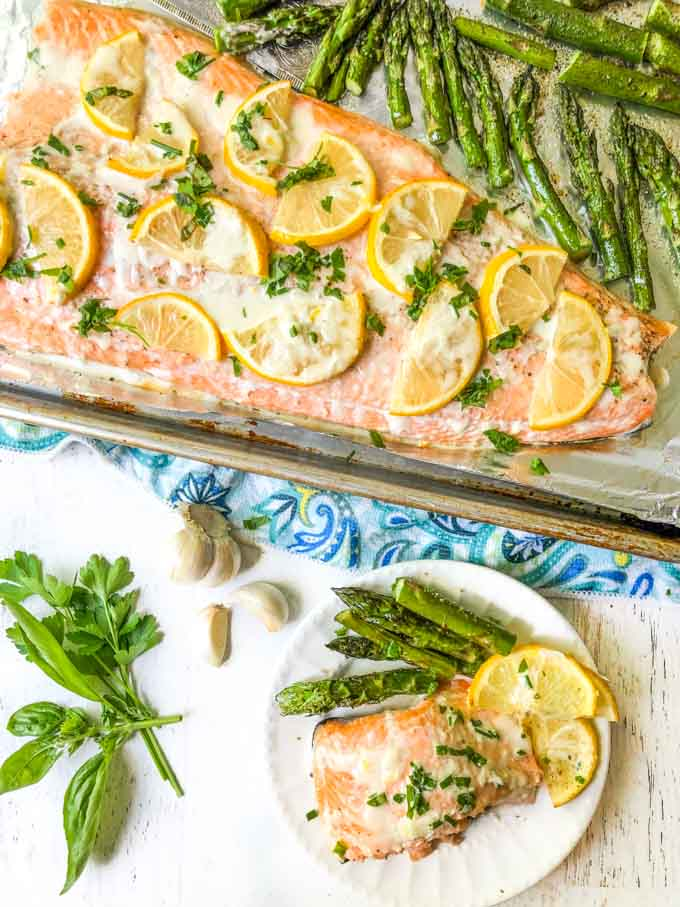 sheet pan with whole salmon covered in lemons, fresh herbs and plate with a serving