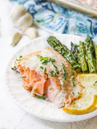 a white plate with a serving easy baked salmon with lemon slices and asparagus