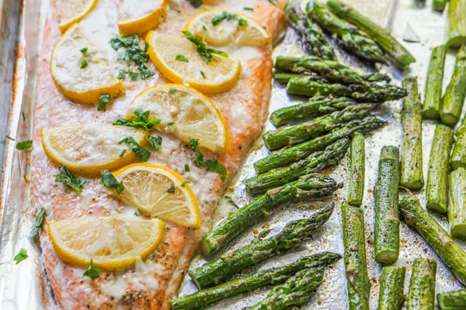 closeup of sheet pan of salmon with asparagus cooked.