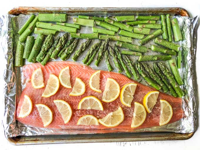 sheet pan with raw asparagus and salmon with lemon slices