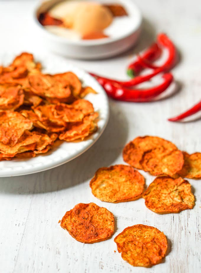 nacho zucchini chips on a white plate and chili peppers in background with spices