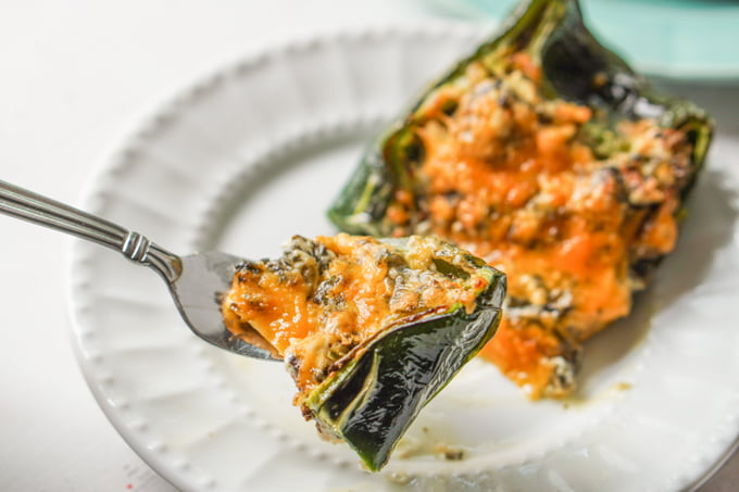 a fork with a bite of stuffed poblano.