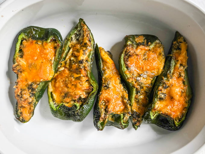 cooked stuffed poblano peppers in white baking dish