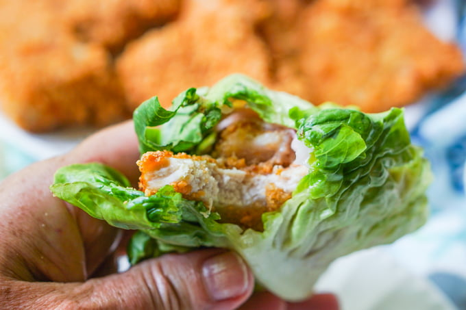 hand holding keto chicken sandwich in lettuce wrap with a bite taken out