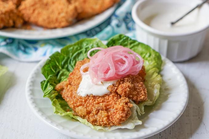 keto fried chicken sandwich using lettuce wrap on white plate