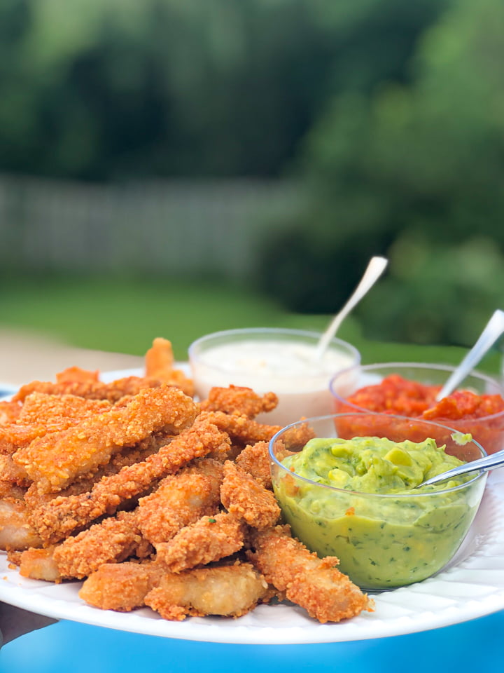 white plate with fried pork chop strips and 3 dipping sauces with backyard in the background
