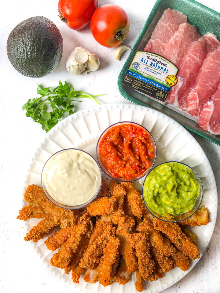 white plate with fried pork chops and dips, an avocado, fresh cilantro, garlic cloves, tomatoes and a package of Smithfield boneless pork chops