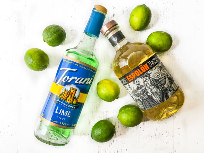 aerial view of a bottle of lime sugar free syrup and a bottle of tequila with limes