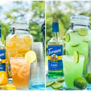 Spiked Iced tea and Margarita punch in large containers with Torani bottles, cups and sliced fruit outside