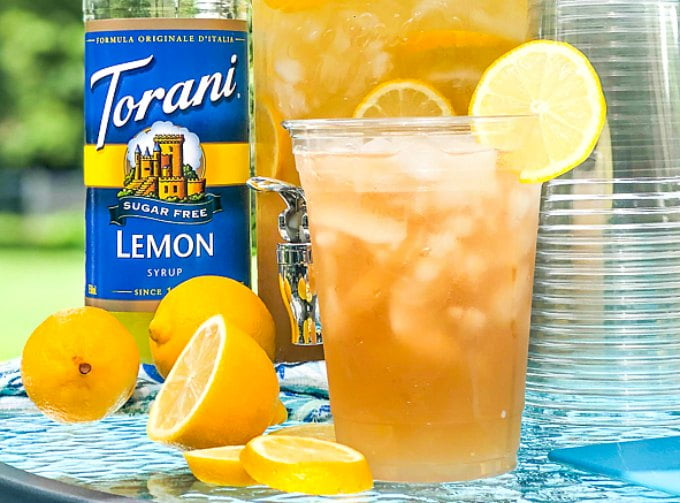 closeup of keto spiked iced tea with a lemon and Torani bottle in background