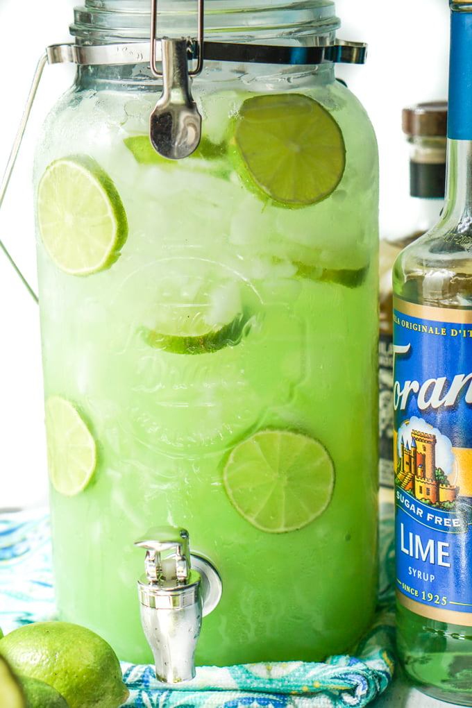 large drink dispenser with keto margarita punch with lime slices
