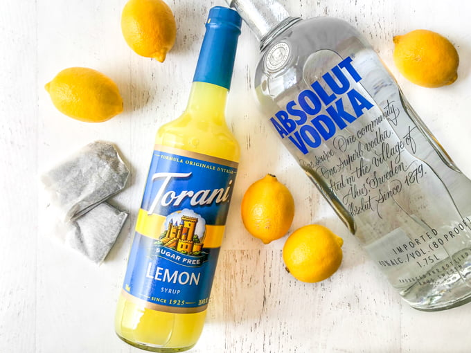 bottle of Torani lemon syrup and a bottle of vodka with lemons and tea bags