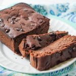 chocolate zucchini bread loaf sliced on white plate with blue towel
