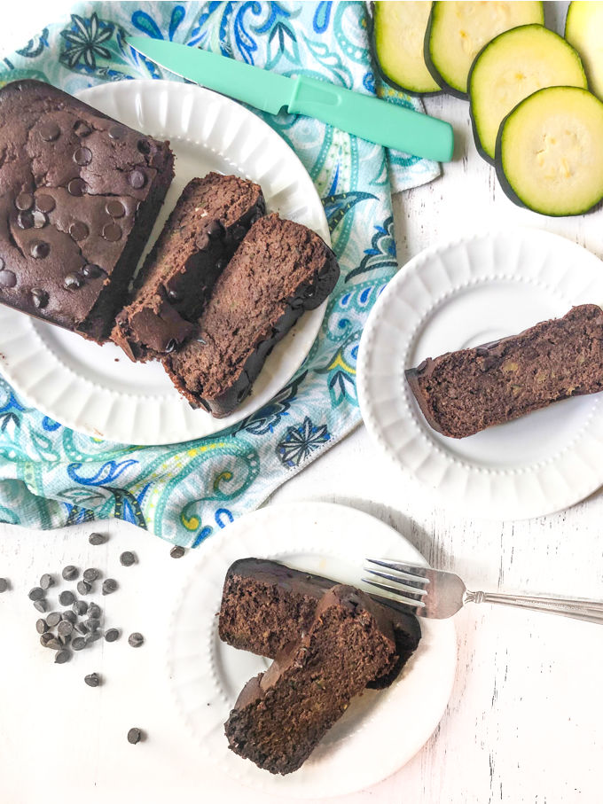 plate with loaf of chocolate keto zucchini bread on blue towel and white plates with single slices, and slices of zucchini raw