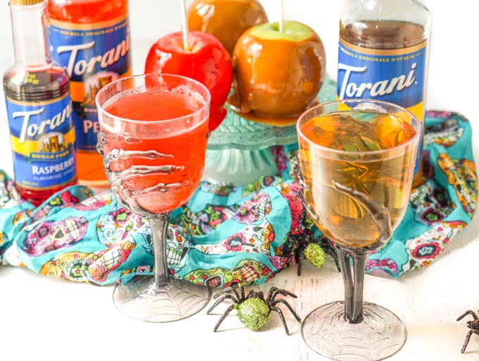 halloween glasses holding low carb candy and caramel apple drinks with apples and Torani bottles in background