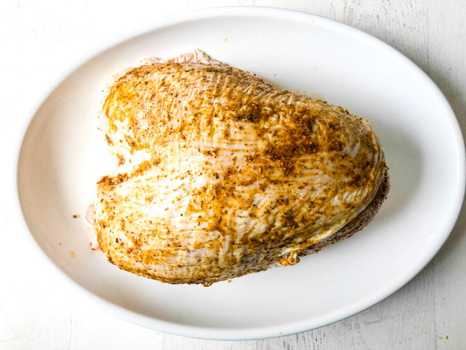 raw turkey breast with rub on it sitting on white platter