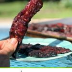 hand holding smoked beef jerky piece outside with text overlay