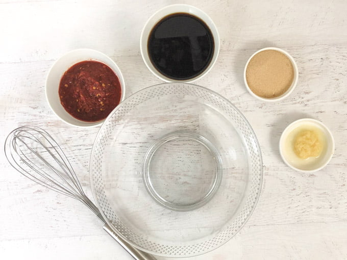 empty glass bowl, whisk and small bowls with ginger, garlic chili sauce, soy sauce and brown sugar