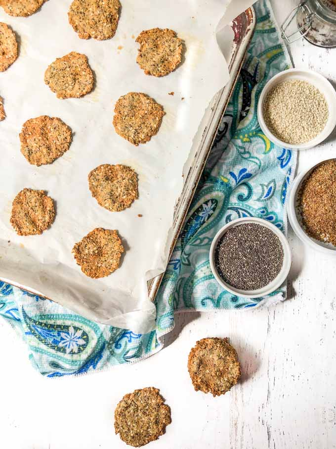 cookie tray with round low carb crackers with blue towel and white bowls with sesame, chia and flax seeds