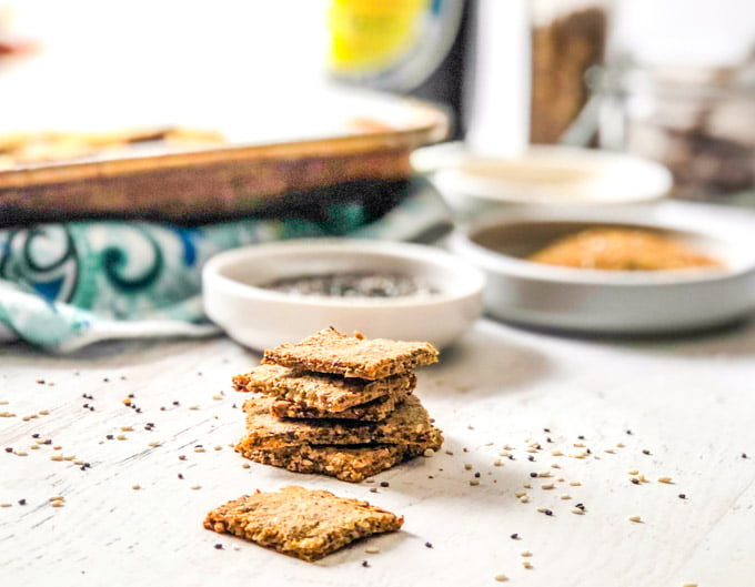 stack of low carb crackers with scatter seeds and cookie tray in background