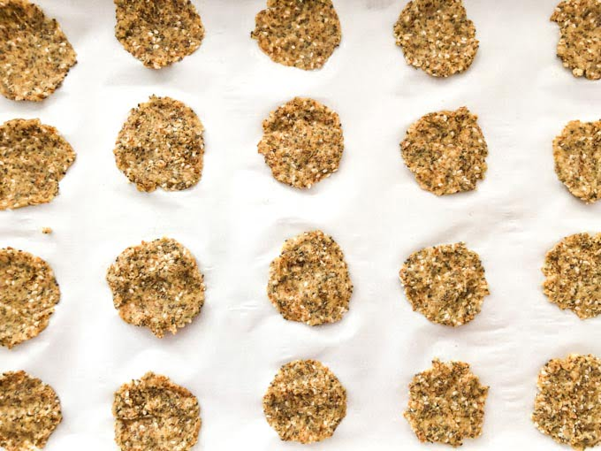 cookie tray with parchment paper with raw round low carb crackers