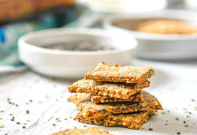 stack of low carb crackers with bowls of chia and flax seeds in background