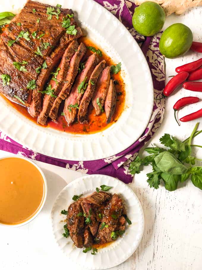 Thai marinated flank steak on white platter and slices on white plate with chiles, limes and low carb peanut dipping sauce