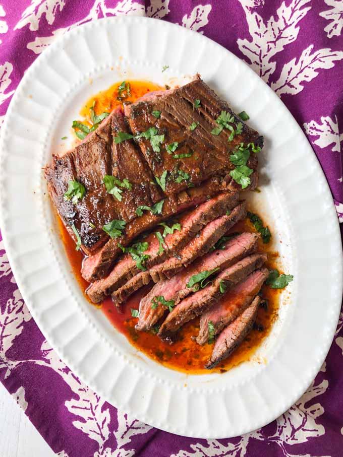 sliced Thai marinated flank steak on white platter on purple tea towel