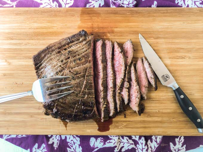 carved marinated flank steak on wooden cutting board with fork and knife