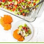 low carb hamburger dip in baking dish and white plate, cheese chips and text overlay