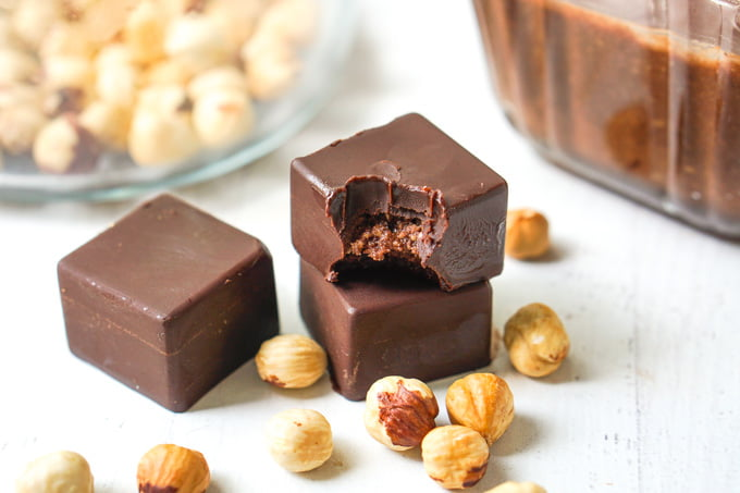 chocolate candy with hazelnut butter in middle and scattered roasted hazelnuts