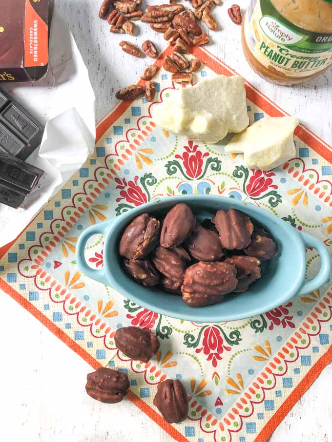 blue bowl with chocolate covered pecan keto candy, cacao butter on printed napkin