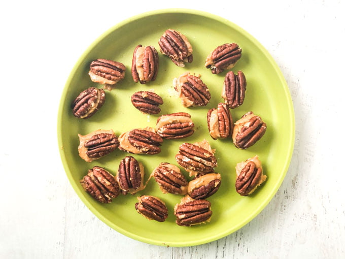 pecans filled with peanut butter on green plate